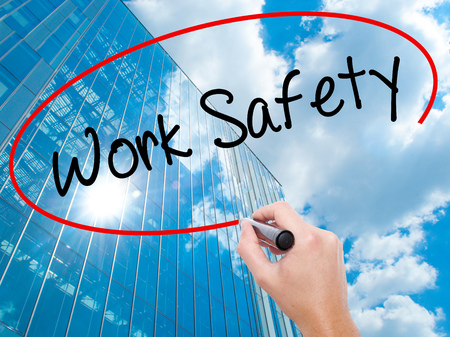 or electrocution: Man Hand writing Work Safety with black marker on visual screen. Business, technology, internet concept. Modern business skyscrapers background. Stock Photo Stock Photo