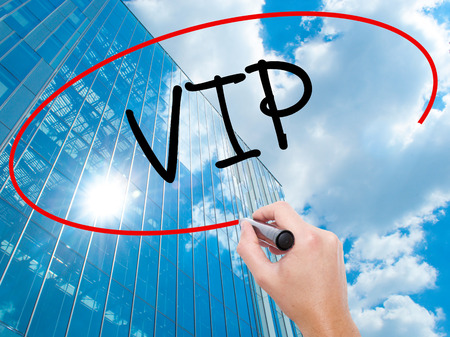 Man Hand writing  VIP with black marker on visual screen.  Business, technology, internet concept. Modern business skyscrapers background. Stock Photo Stock Photo