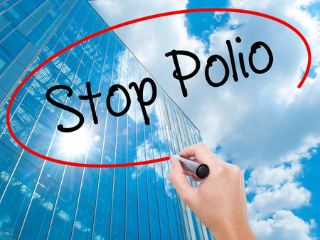 Man Hand writing Stop Polio with black marker on visual screen.  Business, technology, internet concept. Modern business skyscrapers background. Stock Photo