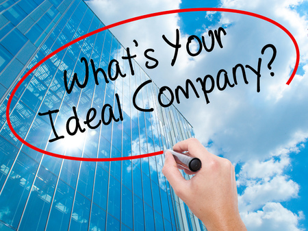 Man Hand writing Whats Your Ideal Company? with black marker on visual screen.  Business, technology, internet concept. Modern business skyscrapers background. Stock Photo Standard-Bild