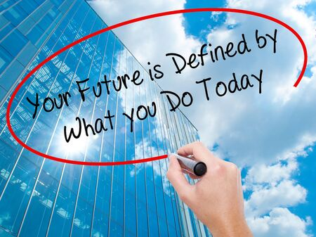 Man Hand writing Your Future is Defined by What you Do Today  with black marker on visual screen. Business, technology, internet concept. Modern business skyscrapers background. Stock Photo