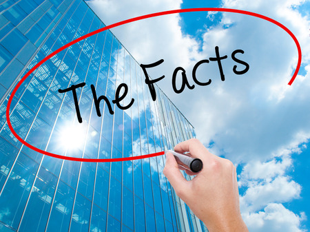 Man Hand writing The Facts  with black marker on visual screen. Business, technology, internet concept. Modern business skyscrapers background. Stock Photo Stock Photo