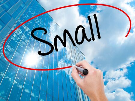 Man Hand writing Small with black marker on visual screen.  Business, technology, internet concept. Modern business skyscrapers background. Stock Photo