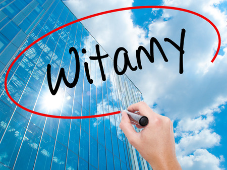 hi back: Man Hand writing Witamy (Welcome in Polish) with black marker on visual screen.  Business, technology, internet concept. Modern business skyscrapers background. Stock Photo