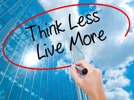 personal perspective: Man Hand writing Think Less Live More with black marker on visual screen.  Business, technology, internet concept. Modern business skyscrapers background. Stock Photo Stock Photo