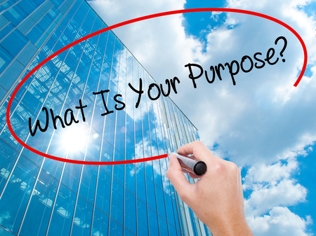 Man Hand writing What Is Your Purpose?  with black marker on visual screen.  Business, technology, internet concept. Modern business skyscrapers background. Stock Photo