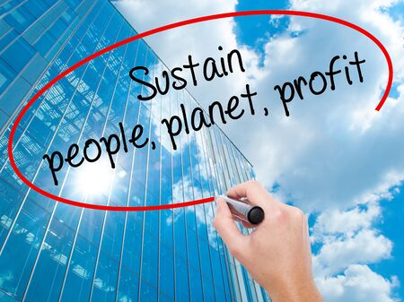economic theory: Man Hand writing Sustain, people, planet, profit with black marker on visual screen. Business, technology, internet concept. Modern business skyscrapers background. Stock Photo