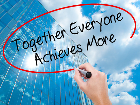 everyone: Man Hand writing Together Everyone Achieves More with black marker on visual screen. Business, technology, internet concept. Modern business skyscrapers background. Stock Photo