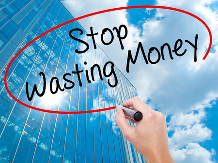 Man Hand writing Stop Wasting Money with black marker on visual screen. Business, technology, internet concept. Modern business skyscrapers background. Stock Photo Stock Photo