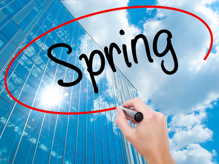 eastertime: Man Hand writing Spring with black marker on visual screen.  Business, technology, internet concept. Modern business skyscrapers background. Stock Photo