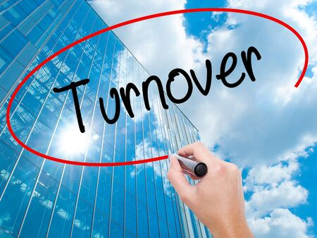 Man Hand writing Turnover with black marker on visual screen. Business, technology, internet concept. Modern business skyscrapers background. Stock Photo