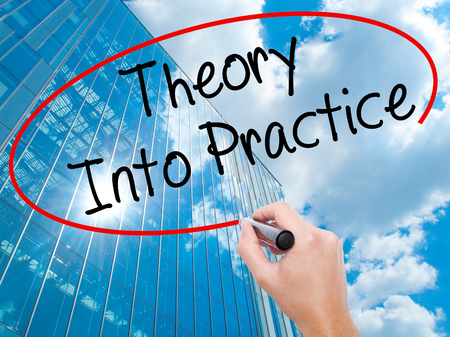 Man Hand writing Theory Into Practice with black marker on visual screen. Business, technology, internet concept. Modern business skyscrapers background. Stock Photo