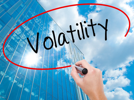 volatility: Man Hand writing Volatility with black marker on visual screen. Business, technology, internet concept. Modern business skyscrapers background. Stock Photo