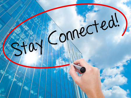 Man Hand writing Stay Connected! with black marker on visual screen. Business, technology, internet concept. Modern business skyscrapers background. Stock Photo