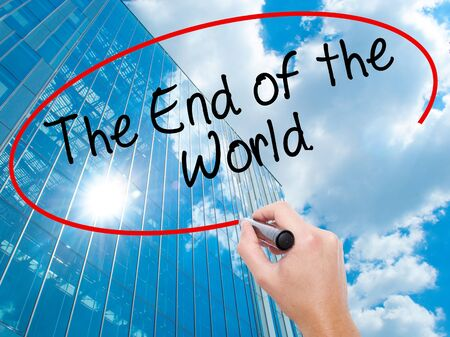 Man Hand writing The End of the World with black marker on visual screen.  Business, technology, internet concept. Modern business skyscrapers background. Stock Photo Stock Photo