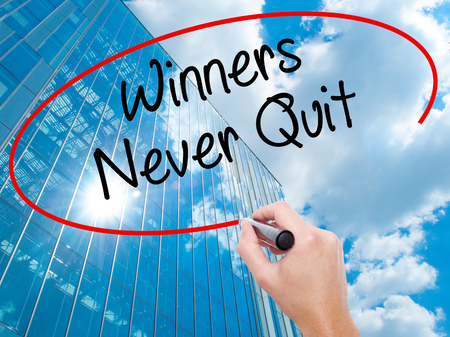 Man Hand writing Winners Never Quit with black marker on visual screen.  Business, technology, internet concept. Modern business skyscrapers background. Stock Photo