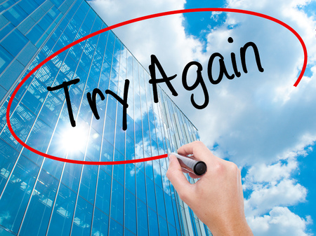 Man Hand writing Try Again with black marker on visual screen.  Business, technology, internet concept. Modern business skyscrapers background. Stock Photo