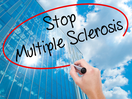 spasms: Man Hand writing Stop Multiple Sclerosis with black marker on visual screen.  Business, technology, internet concept. Modern business skyscrapers background. Stock Photo Stock Photo