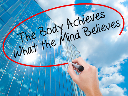 believes: Man Hand writing The Body Achieves What the Mind Believes with black marker on visual screen. Business, technology, internet concept. Modern business skyscrapers background. Stock Photo Stock Photo