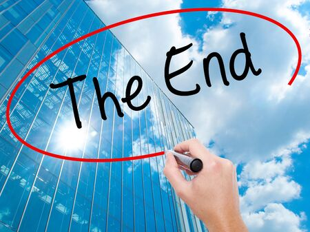 conclusive: Man Hand writing The End with black marker on visual screen. Business, technology, internet concept. Modern business skyscrapers background. Stock Photo
