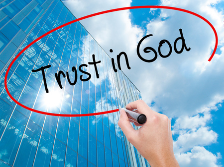 Man Hand writing Trust in God with black marker on visual screen. Business, technology, internet concept. Modern business skyscrapers background. Stock Photo