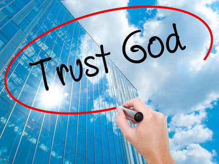 trust in god: Man Hand writing Trust God  with black marker on visual screen. Business, technology, internet concept. Modern business skyscrapers background. Stock Photo Stock Photo