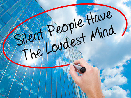 Man Hand writing Silent People Have The Loudest Mind with black marker on visual screen.  Business, technology, internet concept. Modern business skyscrapers background. Stock Photo Stock Photo