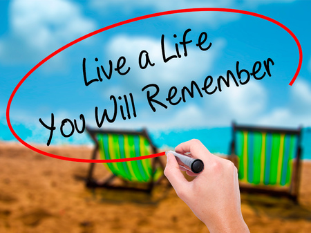 Man Hand writing Live a Life You Will Remember with black marker on visual screen. Isolated on sunbed on the beach. Business, technology, internet concept.