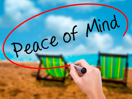 sense of security: Man Hand writing Peace of Mind black marker on visual screen. Isolated on sunbed on the beach. Business, technology, internet concept. Stock Image Stock Photo