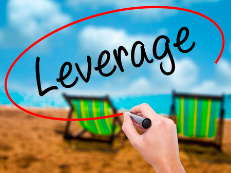 Man Hand writing Leverage with black marker on visual screen. Isolated on sunbed on the beach. Business, technology, internet concept. Stock Photo