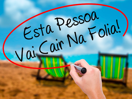 Man Hand writing Esta Pessoa Vai Cair Na Folia! (This Person Will be at Carnaval in Portuguese) with black marker on visual screen. Isolated on sunbed on the beach. Business, technology, internet concept. Stock Photo