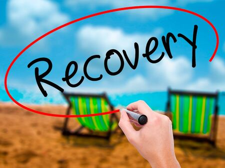 Man Hand writing  Recovery  with black marker on visual screen. Isolated on sunbed on the beach. Life, technology, internet concept. Stock Image Stock Photo