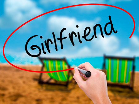 Man Hand writing Girlfriend with black marker on visual screen. Isolated on sunbed on the beach. Business, technology, internet concept.