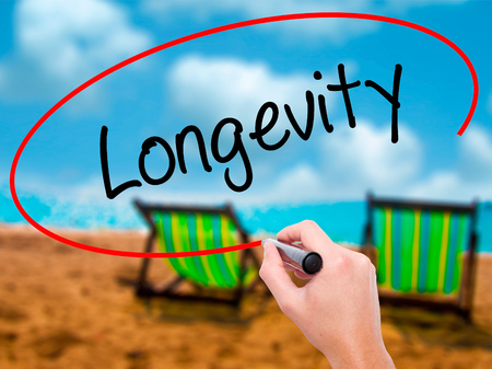 Man Hand writing Longevity  with black marker on visual screen. Isolated on sunbed on the beach. Business, technology, internet concept. Stock Photo
