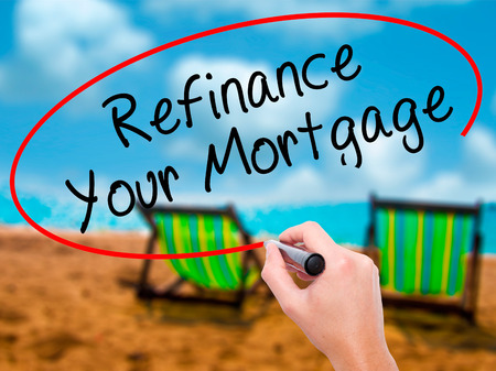 loaning: Man Hand writing Refinance Your Mortgage with black marker on visual screen. Isolated on sunbed on the beach. Business, technology, internet concept. Stock Image Stock Photo