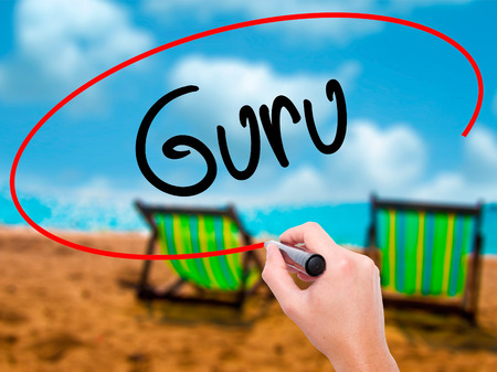Man Hand writing Guru with black marker on visual screen. Isolated on sunbed on the beach. Business, technology, internet concept. Stock Photo Stock Photo