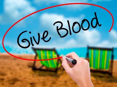 Man Hand writing Give Blood  with black marker on visual screen. Isolated on sunbed on the beach. Business, technology, internet concept.