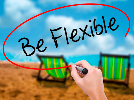Man Hand writing Be Flexible with black marker on visual screen. Isolated on sunbed on the beach. Business, technology, internet concept. Stock Photo