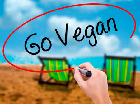 Man Hand writing Go Vegan with black marker on visual screen. Isolated on sunbed on the beach. Business, technology, internet concept. Stock Photo Stock Photo