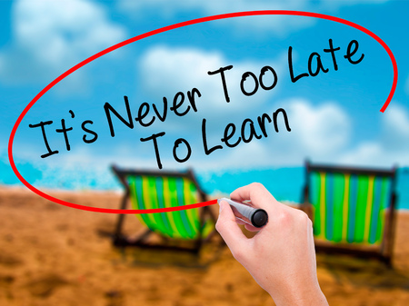 Man Hand writing Its Never Too Late To Learn with black marker on visual screen. Isolated on sunbed on the beach. Business, technology, internet concept. Stock Photo Stock Photo