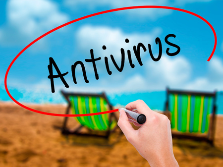 Man Hand writing Antivirus   with black marker on visual screen. Isolated on sunbed on the beach. Business, technology, internet concept. Stock Photo Stock Photo