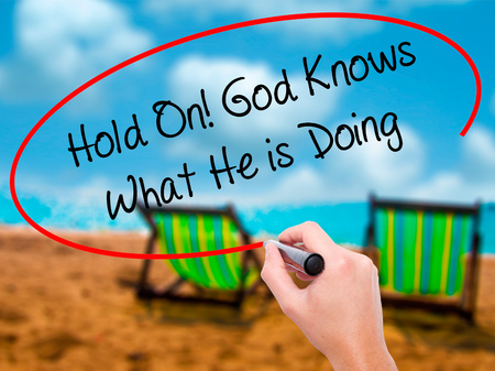 confessing: Man Hand writing Hold On! God Knows What He is Doing with black marker on visual screen. Isolated on sunbed on the beach. Business, technology, internet concept.