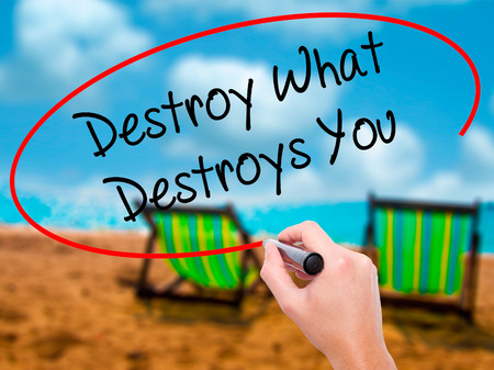 annihilate: Man Hand writing Destroy What Destroys You with black marker on visual screen. Isolated on sunbed on the beach. Business, technology, internet concept. Stock Photo