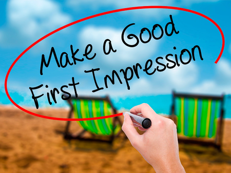 pioneering: Man Hand writing Make a Good First Impression with black marker on visual screen. Isolated on sunbed on the beach. Business, technology, internet concept. Stock Photo
