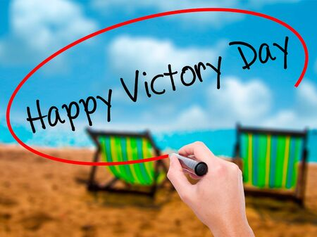 Man Hand writing Happy Victory Day with black marker on visual screen. Isolated on sunbed on the beach. Business, technology, internet concept. Stock  Photo