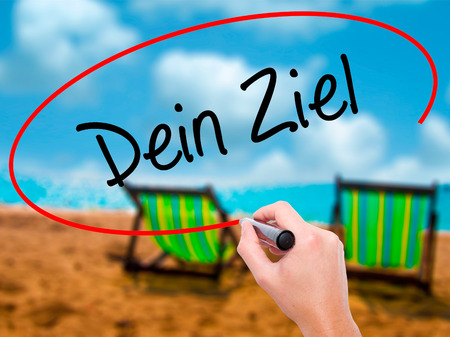 Man Hand writing Dein Ziel (Your Goal in German)  with black marker on visual screen. Isolated on sunbed on the beach. Business, technology, internet concept. Stock Photo