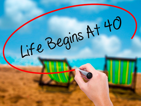 Man Hand writing Life Begins At 40  with black marker on visual screen. Isolated on sunbed on the beach. Business, technology, internet concept. Stock Photo