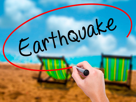 Man Hand writing Earthquake with black marker on visual screen. Isolated on sunbed on the beach. Business, technology, internet concept. Stock Photo