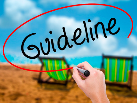 Man Hand writing Guideline with black marker on visual screen. Isolated on sunbed on the beach. Business, technology, internet concept. Stock Photo