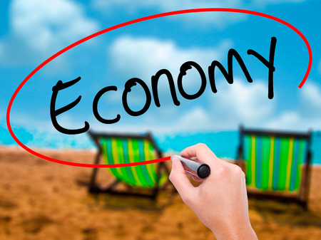 Man Hand writing Economy with black marker on visual screen. Isolated on sunbed on the beach. Business, technology, internet concept. Stock Photo